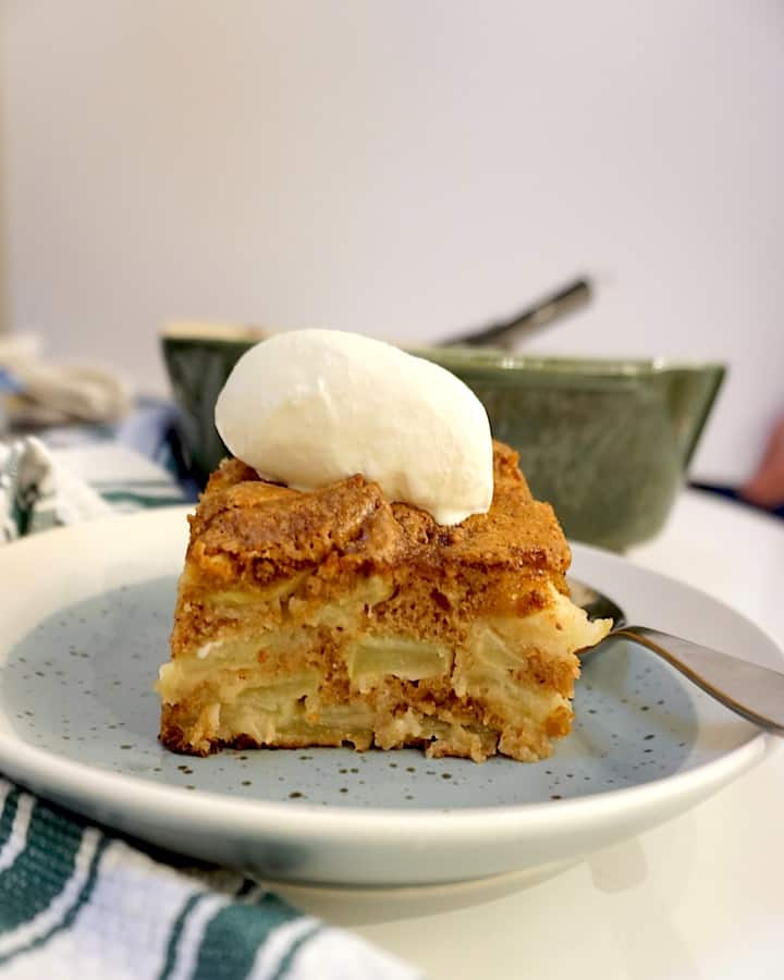 apple cake with vanilla ice cream on top on a bluish plate with a spoon on the plate