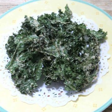 Green sour cream onion kale chips on yellow plate