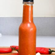 red hot sauce in glass bottle with black cap surrounded by red chili peppers and garlic on wood cutting board