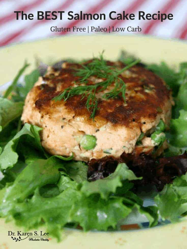 Salmon Cake on a bed of greens on a yellow plate