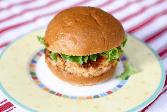 Salmon cake on a brioche bun on a yellow plate sitting on a red and white striped kitchen towel