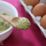 Avocado mask mixture on a wooden spoon rests on a white bowl on the pink placemat with eggs in the background