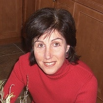 smiling short brown haired woman wearing red sweater