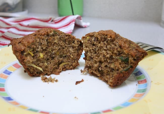 Zucchini Banana Flax Muffins cut in half on yellow plate