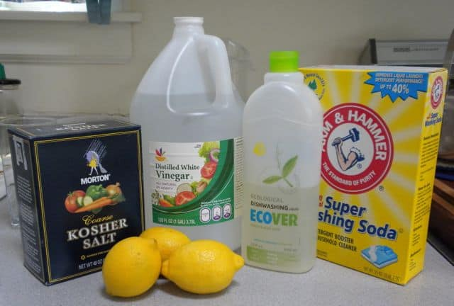 kosher salt next to white vinegar, dishwashing soap, washing soda, and lemons