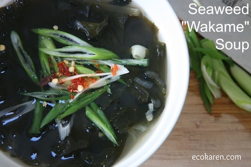 Wakame soup in white bowl with scallions and pepper flake garnish