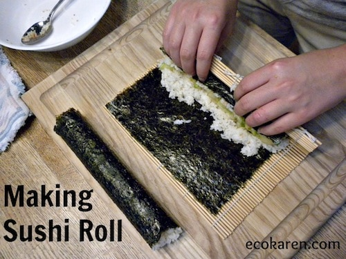 rolling rice in nori on sushi mat on wooden cutting board
