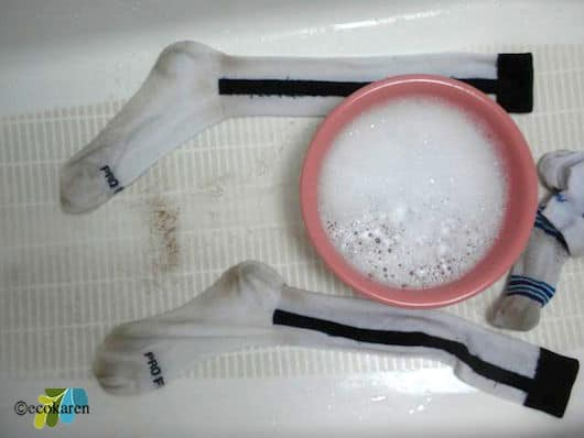 solution of water, liquid laundry detergent, washing soda, hydrogen peroxide, and lemon juice in pink bowl between cleaned white socks in bathtub