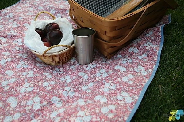 picnic basket and fruit basket on top of Waterproof Picnic Blanket