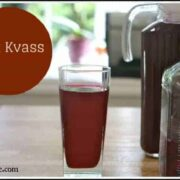 Glass of red beet kavas on a wooden table