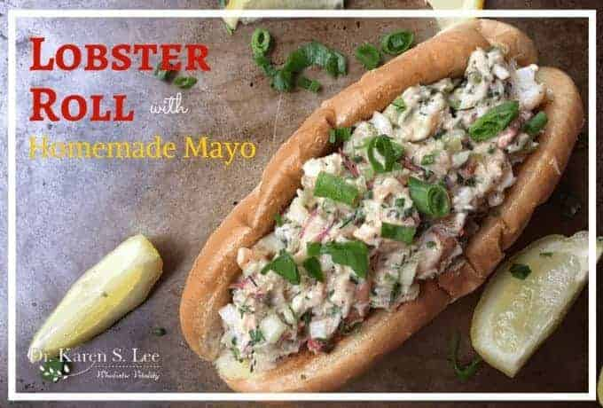 Lobster Roll topped with sliced scallions next to lemon wedges