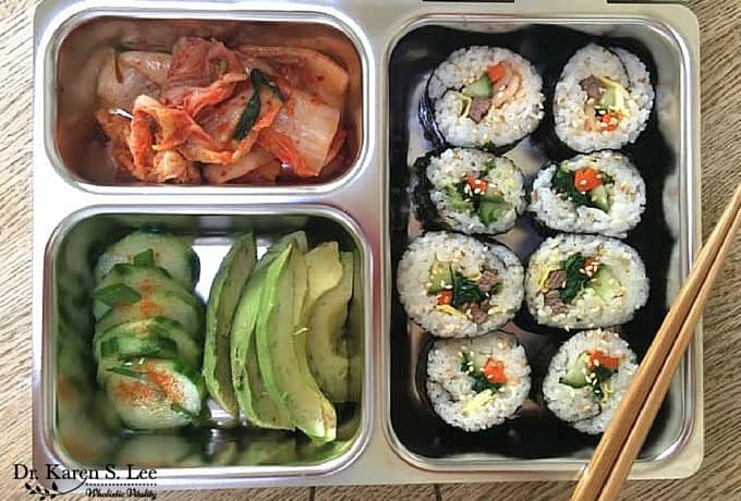 Gimbap, sliced avocado, kimchi in stainless steel bento style lunch box