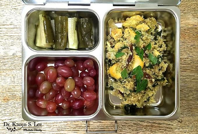 Quinoa, pickles, grapes in stainless steel bento style lunch box