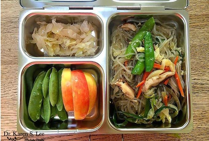 japchae, sugar snaps, slice apples, sauerkraut in stainless steel bento style lunch box