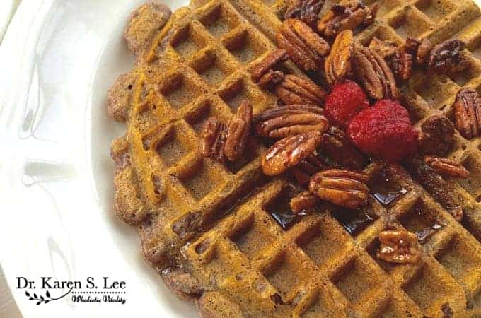 Paleo Pecan Waffle topped with pecans and raspberry on white plate