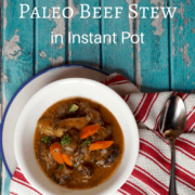 beef stew in white bowl on a red and white stripe kitchen towel