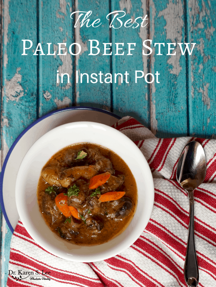 Paleo beef stew in white bowl next to spoon on red white stripe towel