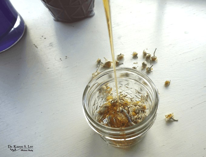 honey pouring into jar of chamomile flowers