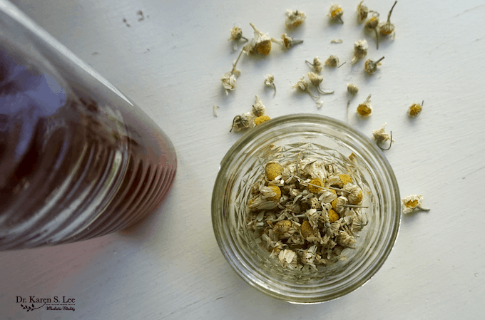 Honey bottle next to glass jar with Chamomile flowers