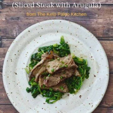 Sliced Steak and Arugula on whitish plate with brown specks on brown wooden plank