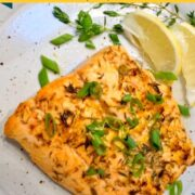 Toasted Coconut Salmon with scallion garnish on a plate with a lemon slice next to it