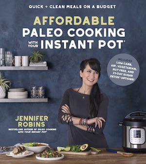 dark haired woman smiling with her arms crossed with food and Instant Pot on table