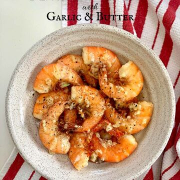 Cooked Shrimp on a white dish on red and white stripe kitchen towel