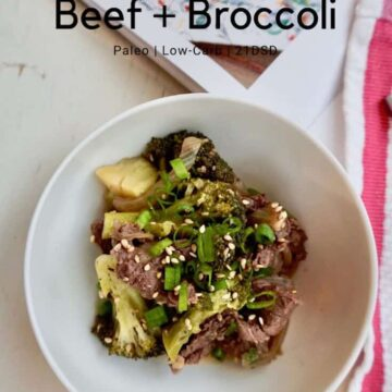 beef and broccoli on a white bowl with red and white towel in the background