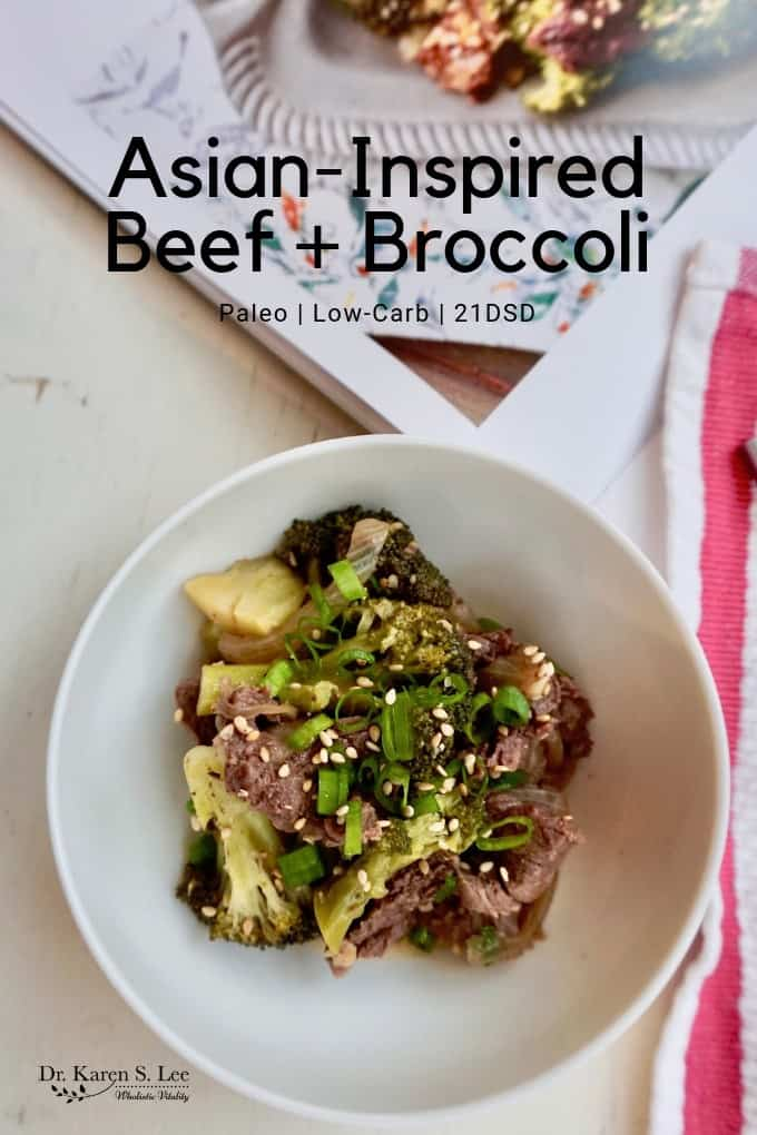 Beef and Broccoli in a while plate with scallions and sesame seeds garnish red striped napkin on the side