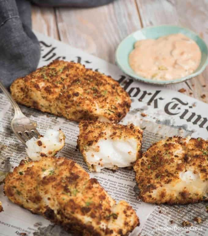 fried white fish pieces with one opened laying on the New York Times newspaper with cajun mayo in a greenish shallow bowl