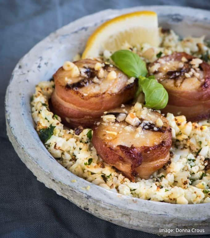 3 bacon wrapped scallops on a bed of white cauli couscous with a lemon wedge and basil on a greyish plate