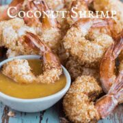 Fried coconut shrimp on a blue wooden plank with one shrimp in a small bowl of sauce