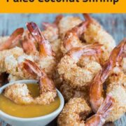 Coconut shrimp on bluish background with one shrimp in dipping szuce