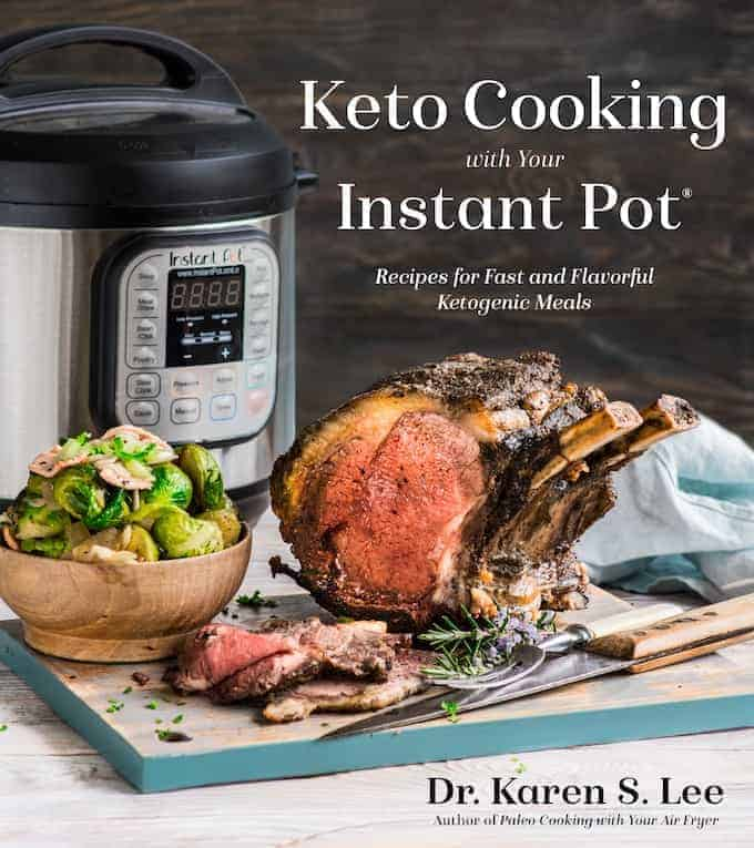 Prime Rib Roast on a wooden board with a bowl of Brussels Sprouts with Instant Pot pressure cooker in the background on the cover of KetoCooking with your Instant Pot cookbook