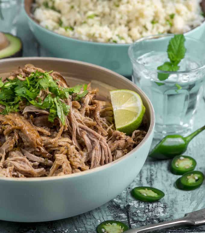 shredded pork in a round platter with lime wedge and cilantro on top