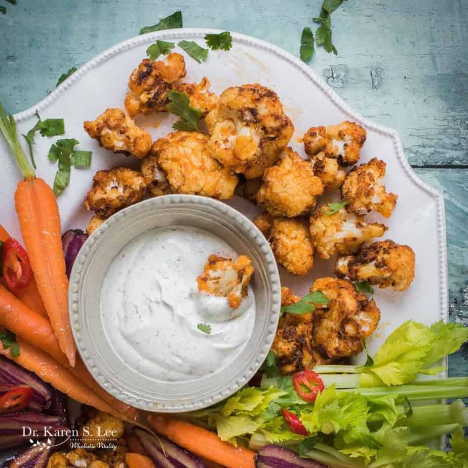Buffalo Cauliflower Bites with assorted vegetables around ranch dressing bowl