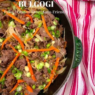 Brown beef slices with slivers of carrots and chopped scallions on a cast iron skillet with red and white stripe napkin in the background