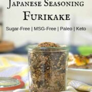 Japanese seasoning furikake with nori in a glass jar on yellow and white stripe kitchen towel with title Japanese Seasoning Furikake above the jar