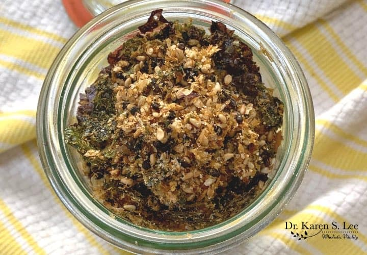 Japanese seasoning furikake with nori in a glass jar on yellow and white stripe kitchen towel