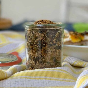 Furikake in a glass jar on a yellow and white stripe kitchen towel