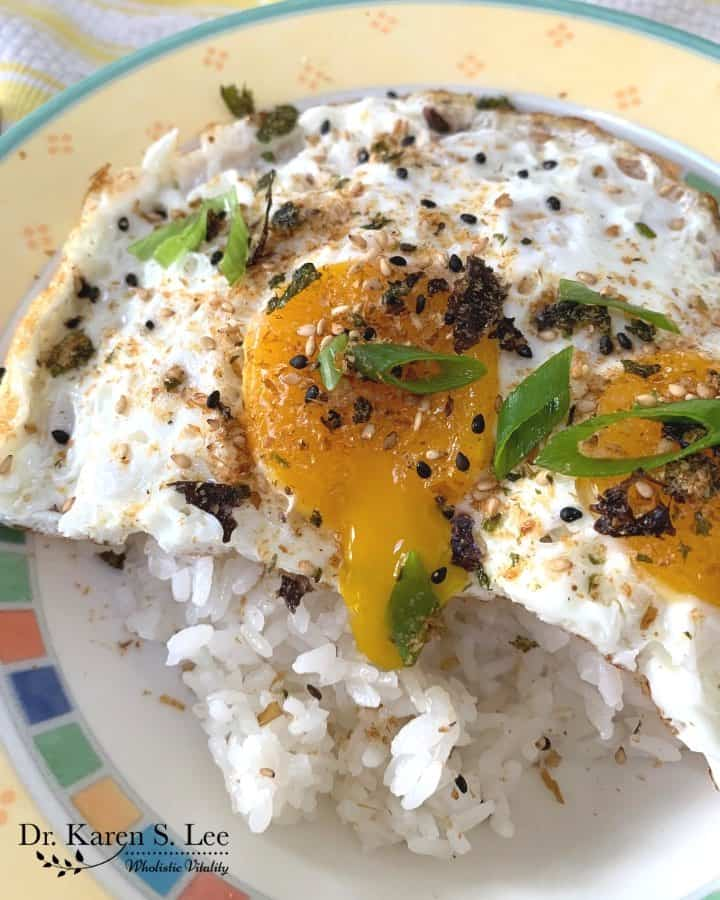 Furikake sprinkled on a plate of white rice and sunny side up eggs with runny yolk