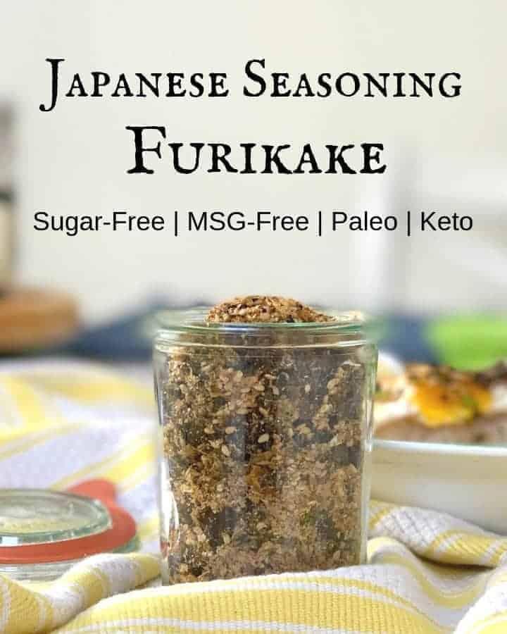 Japanese seasoning furikake with nori in a glass jar on yellow and white stripe kitchen towel with title Japanese Seasoning Furikake above the jar