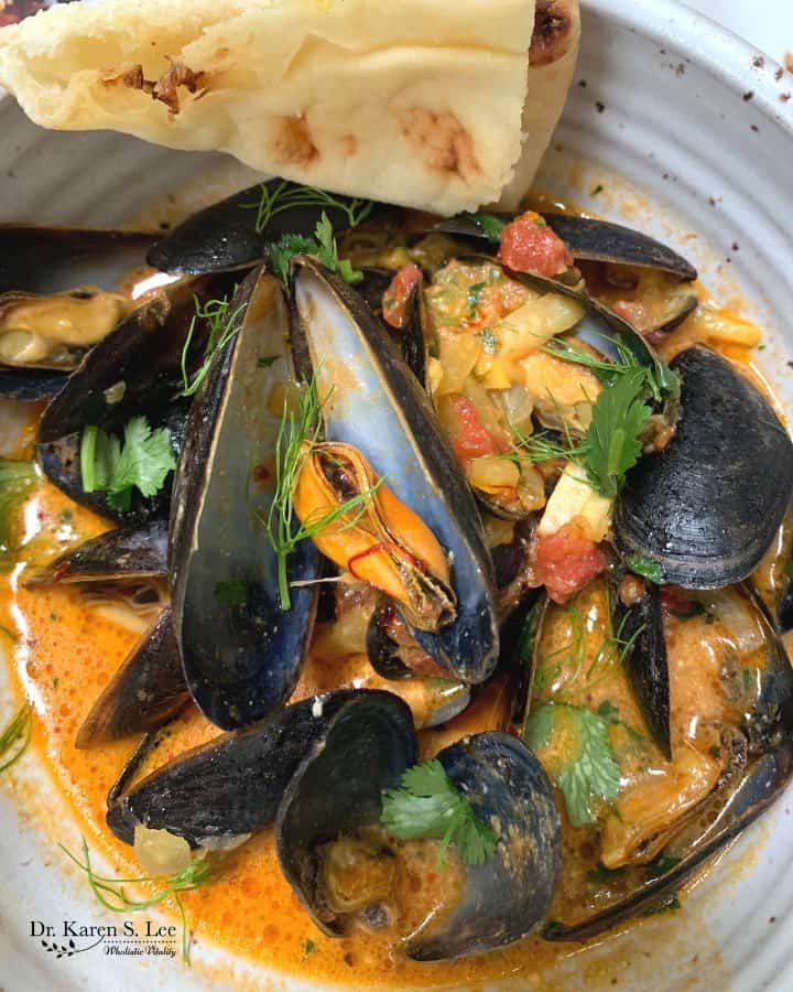 Mussels in saffron colored brodo with tomato pieces