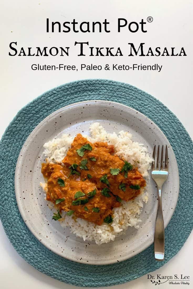 Salmon Tikka Masala in curry sauce over white rice on a speckled whitish plate on a round moss green placemat with a stainless steel fork on the right