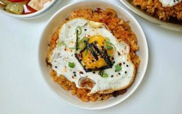 White bowl of kimchi pork fried rice on a white table