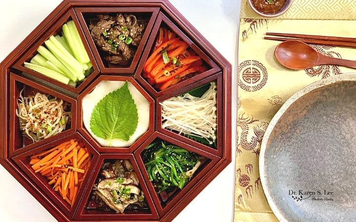 Brown platter Gu Jeol Pan with 9 sections holding colorful vegetables and meat with white radish slices