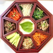 Brown wooden platter with nine sections filled with Korean vegetables with white radish slices in the middle