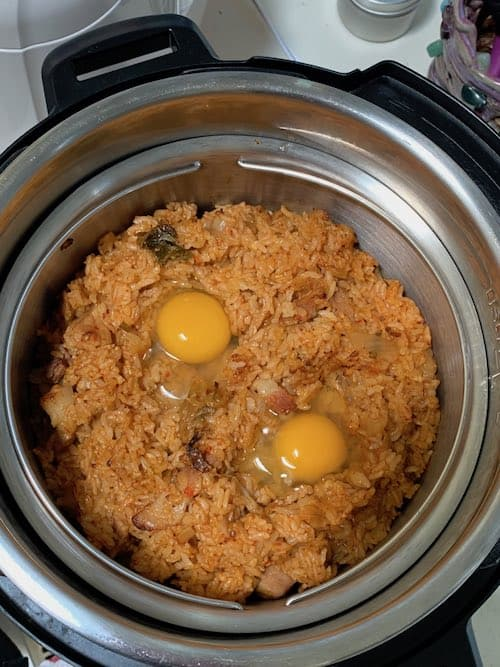 two cracked eggs on kimchi fried rice in multipot