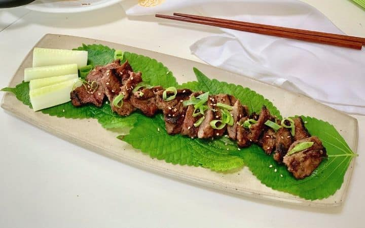 barbecued beef pieces on green vegetables on a cream color oblong shaped platter with brown chopsticks in the background