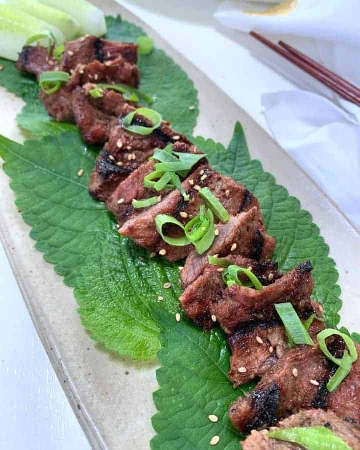 korean bbq galbi pieces on green perilla leaves on a beige platter